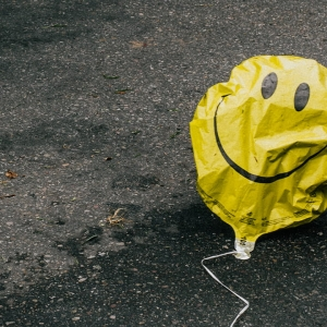 A partly deflated smiley face balloon on a street