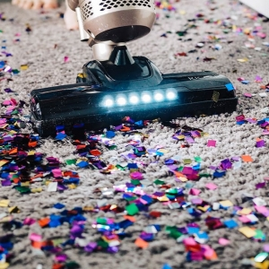 A vacuum cleaner trying to hoover some confetti
