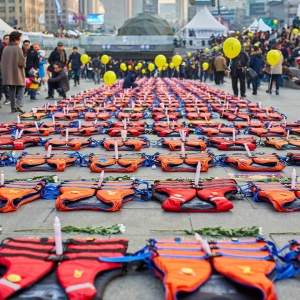 Lines of lifejackets lying on the ground with candles on them