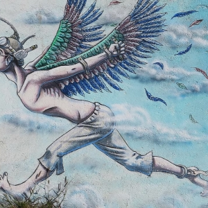 Street art of a man with wings strapped to his arms and chain around his ankle running after a bag of money in front of him