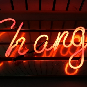 Photo of a red neon sign of the word 'Change'