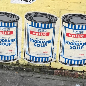 Street art of cans in style of Tesco saying 'Tories value - cream of foodbank soup'