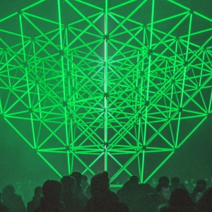 Photo of a green, geometric, neon shape surrounded by people
