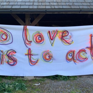 Banner saying 'To love is to act'