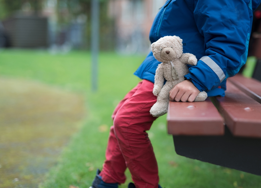 Photo of a child sat on a bench with a teddy bear in hand