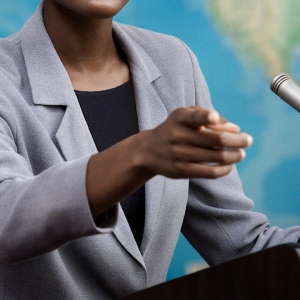 Image of woman at podium pointing, from cover of 'Women of Power'