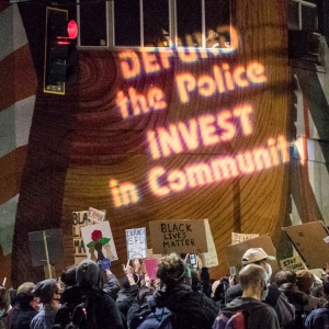 Protest with 'Defund the police, invest in community' projected on the wall