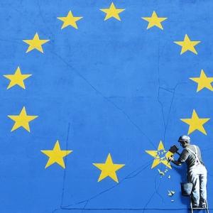 Street art of man destroying EU stars