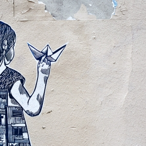 Street art of girl with paper boat