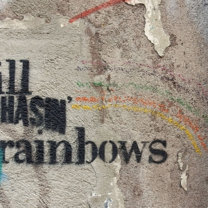 Street art saying 'Still chasin' rainbows'