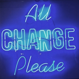 Neon sign saying 'All change please'
