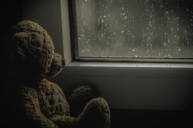 Teddy bear by rainy window