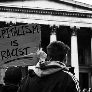 Protest sign saying 'Capitalism is racist'
