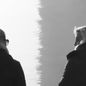 Two women talking by water