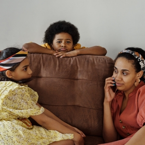 Mother on phone with two children on sofa