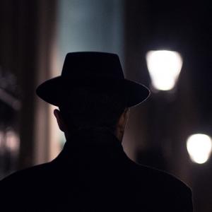 A man walking on a dark street wearing a hat