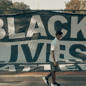 Man walking in front of BLM flag