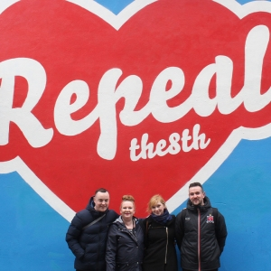 People standing in front of street art saying 'Repeal the 8th'