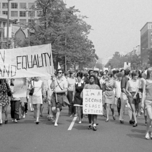 Protesters holding sign saying 'Women demand equality'