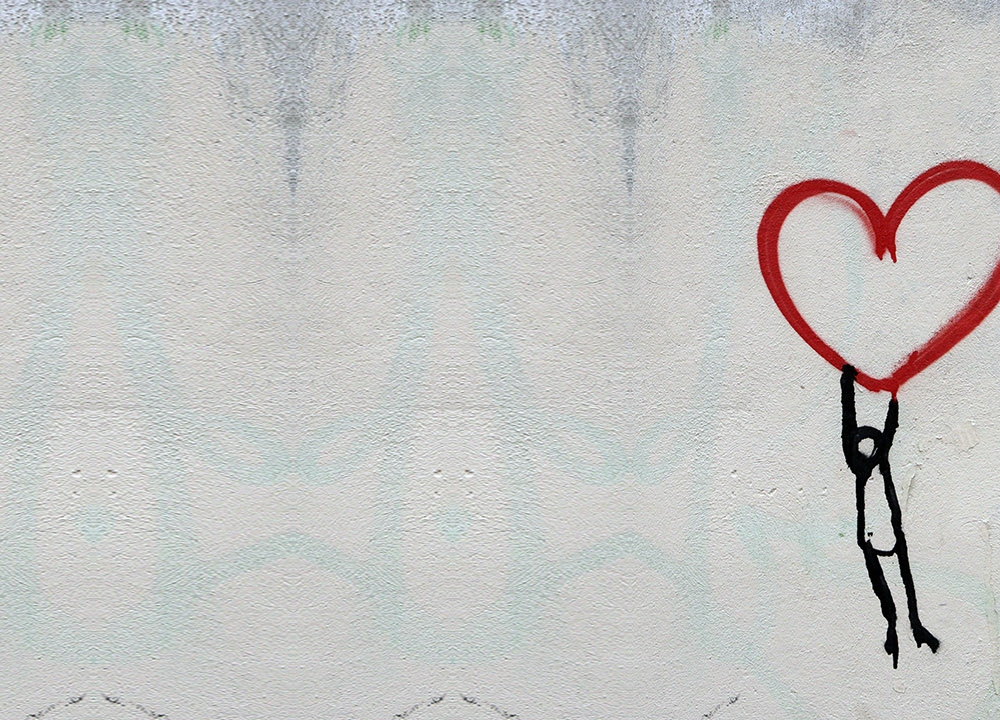 Graffiti of person hanging on to a floating heart
