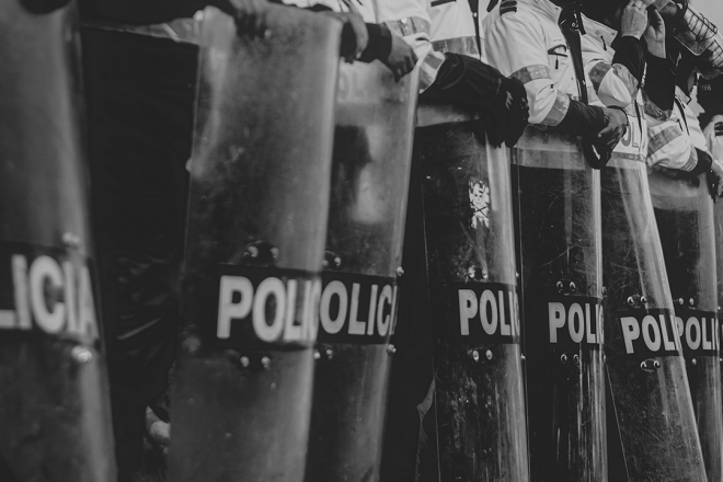 A row of police with riot shields