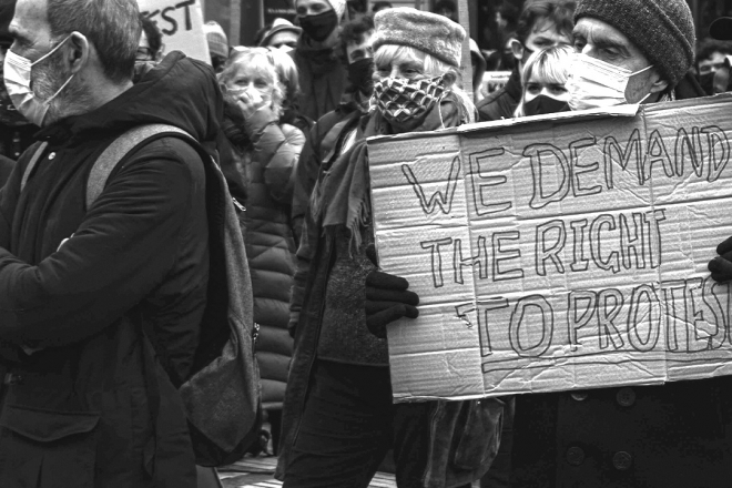 Man holding sign saying 'We demand the right to protest'