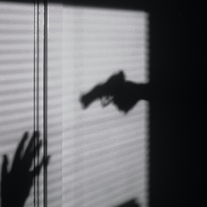 Silhouette of gun and hands up
