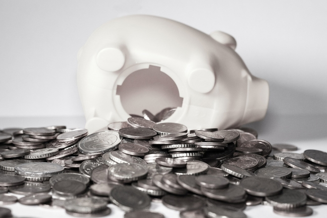 Open piggy bank, with coins spilling out.