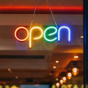 Neon light open sign on a door.