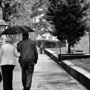 Couple walk through the rain.