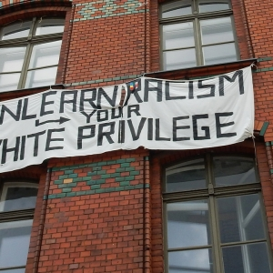 Unlearn racism followed by an arrow to your white privilege on a banner.