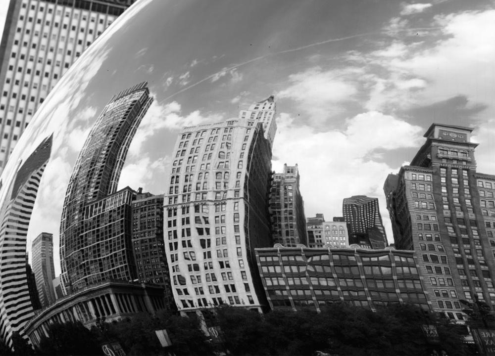 City reflecting off a metal globe.