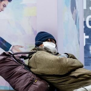 Homeless man sleeping in mask.