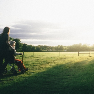 Older lady being pushed through a field in a wheelchair.