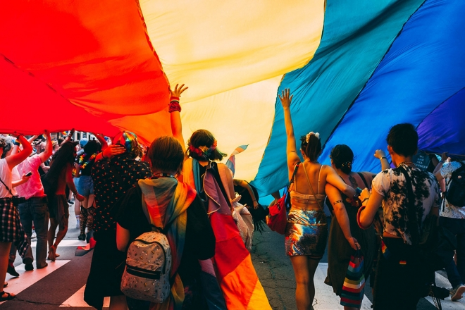 Pride march with giant pride flag above their heads.