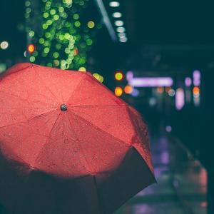 Person holding a red umbrella in the dark