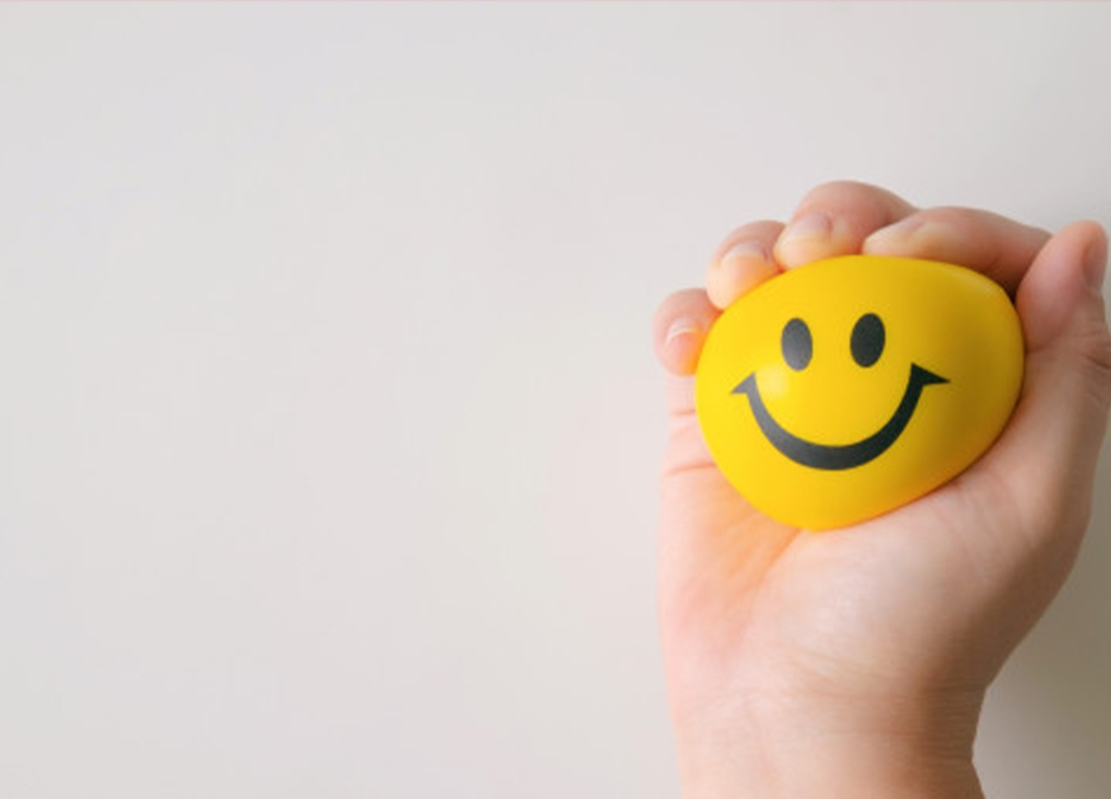 Hand squeezing yellow stress ball with smiley face on it.