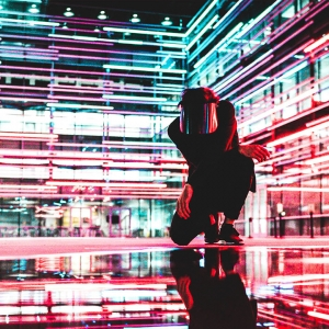Crouching person with mask in in red lights