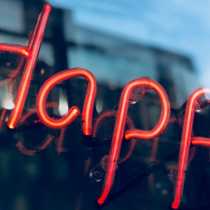 Read neon sign that says happy.