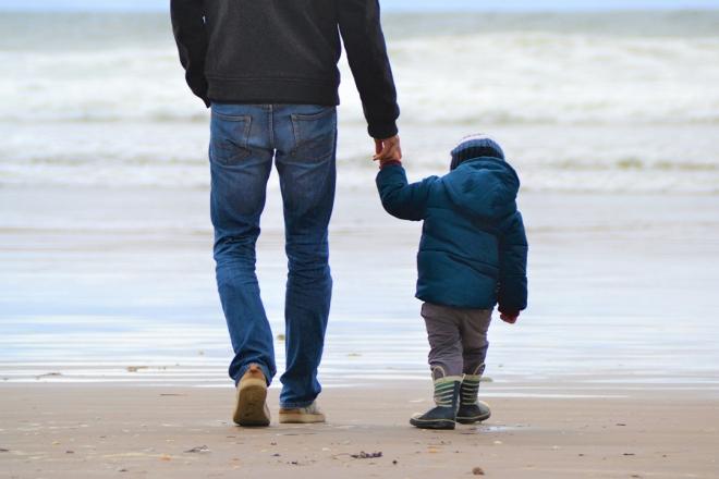 Man walking on beach with kid.