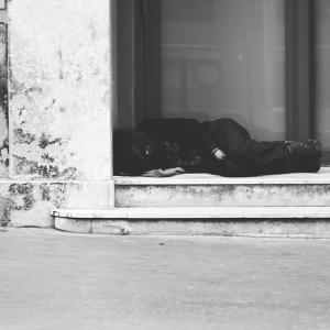 Homeless man asleep in a doorway.