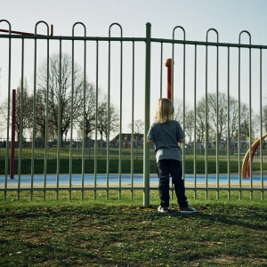 Girl standing outside the fence of a park.