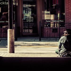 Homeless man sat in doorway.