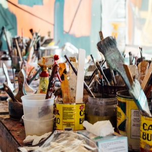 A table covered in paintbrushes and paint.